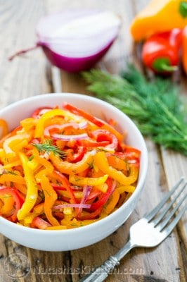 A bowl of zesty mini bell pepper salad with a fork, dill, mini peppers and purple onion beside it
