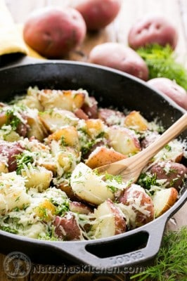 A skillet of buttered red potatoes garnished with parmesan and dill