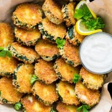 A close up of a skillet with crisp zucchini bites with garlic aioli dip