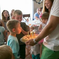 A group of children watching a boy blow out birthday candles on a cake held by his father