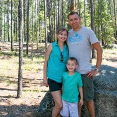 Natasha, her husband and son standing with trees behind them