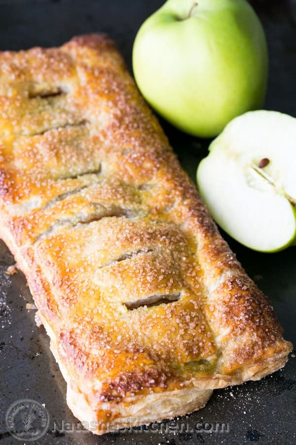 Caramelized apples wrapped in flaky puff pastry dough. So EASY and delicious! | natashaskitchen.com