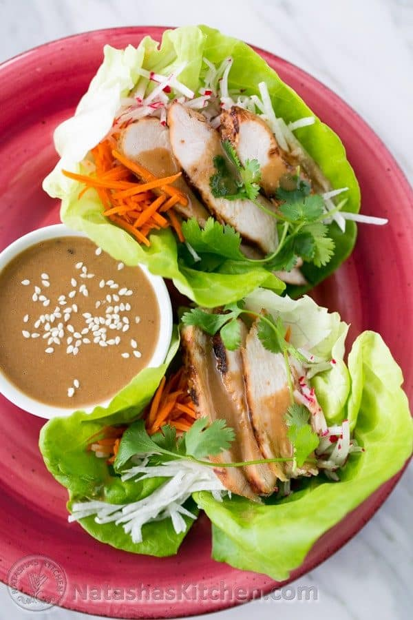 A red plate with Terah\'s delicious lettuce wraps with a little bowl of sauce beside them