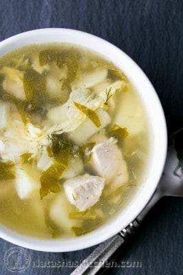 A white bowl of shchavel borshct, sorrel soup