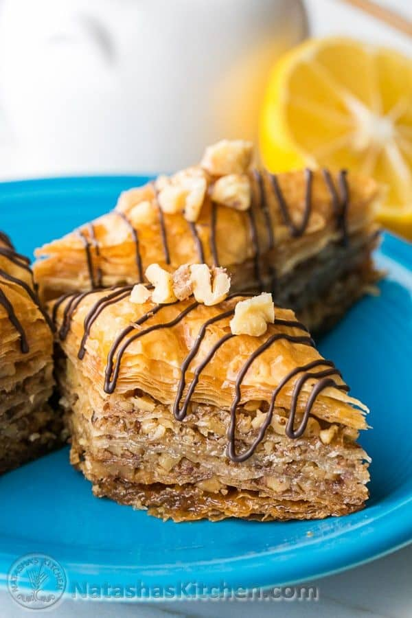 Baklava pieces loaded with nuts and honey lemon syrup with chocolate garnish - A center cut view of this homemade baklava recipe showing flaky, crisp, tender layers.