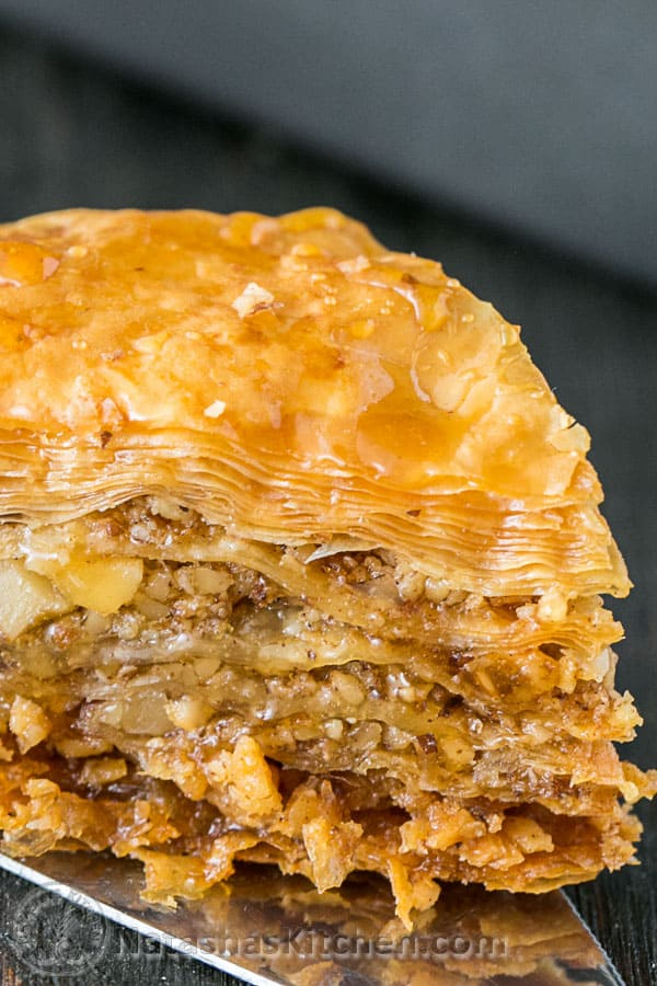 Up close view of baklava recipe showing nut and syrup filling with flaky crisp crust.