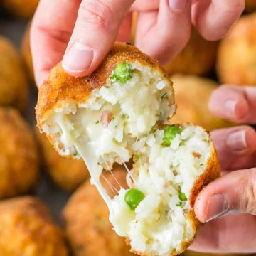 Arancini rice ball broken in half to see melted cheese and rice center