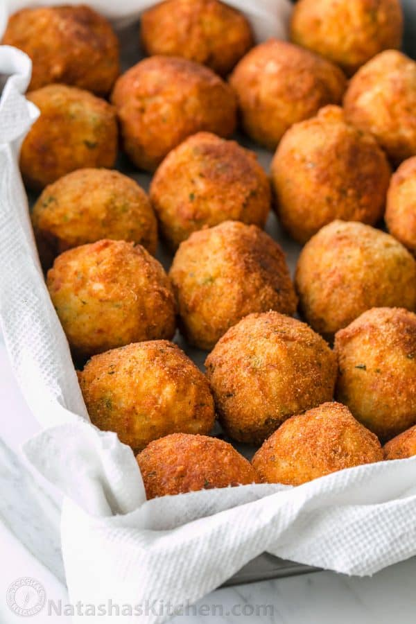 Fried arancini rice balls on a paper towel lined platter
