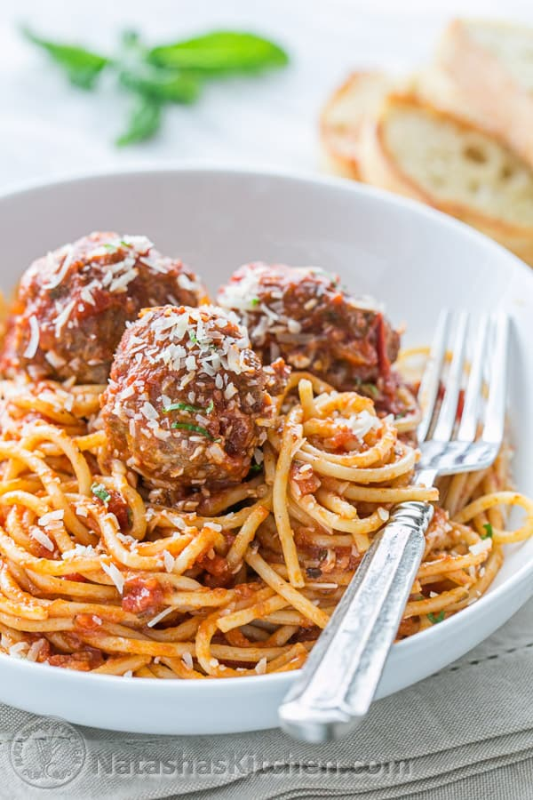 Spaghetti and meatballs served on a plate garnished with parmesan cheese