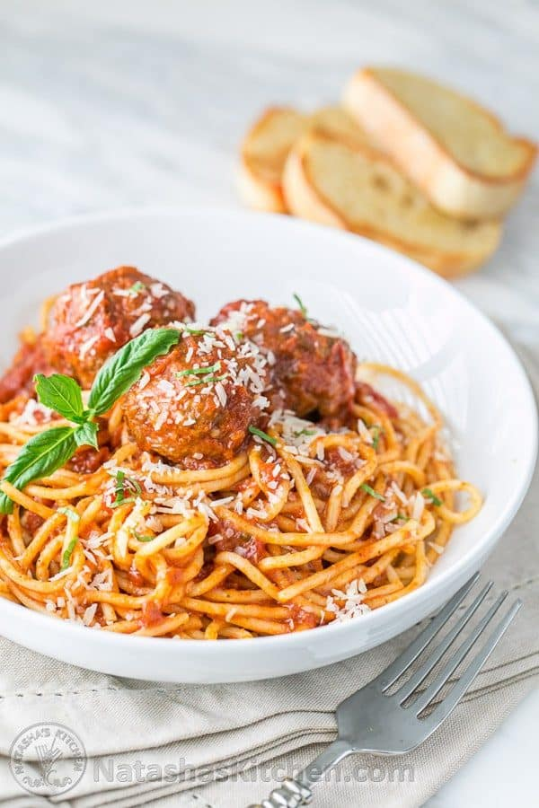 The Best Spaghetti and Meatballs recipe in a bowl topped with parmesan and basil