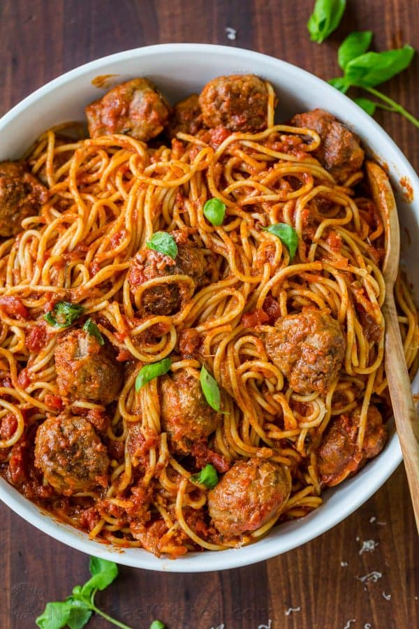 Spaghetti and Meatballs served family style garnished with basil