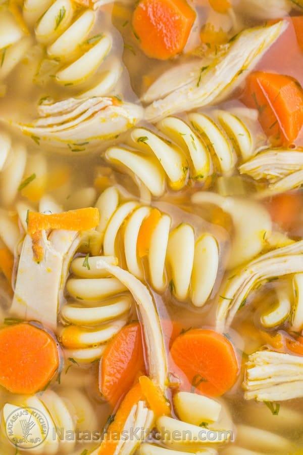 Primer plano de fideos rellenos, zanahorias sabrosas y pollo desmenuzado húmedo en sopa de fideos con pollo
