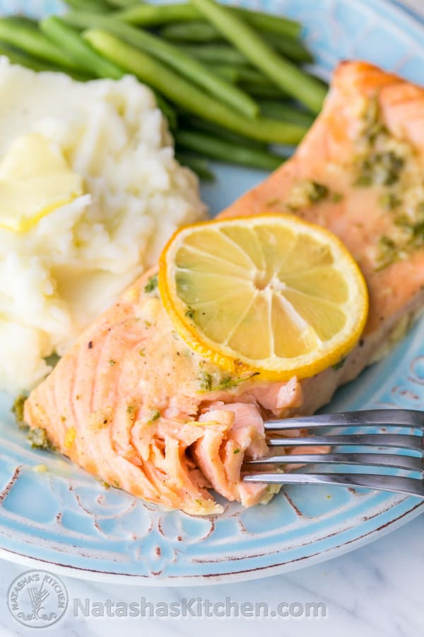 A plate with salmon, mashed potatoes and green beans