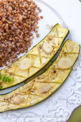Baked zucchini with garlic and lemon on a plate with buckwheat