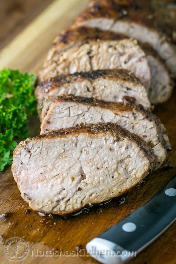 Pork tenderloin sliced against the grain on a cutting board showing juicy tender center