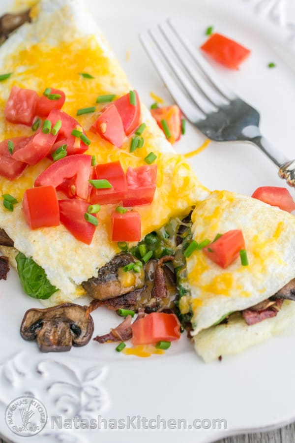 This fluffy egg white omelette is loaded with bacon, mushrooms, cheese, and fresh spinach which softens perfectly inside the omelette. So satisfying! | NatashasKitchen.com