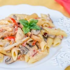 A plate of chicken and vegetable penne alfredo
