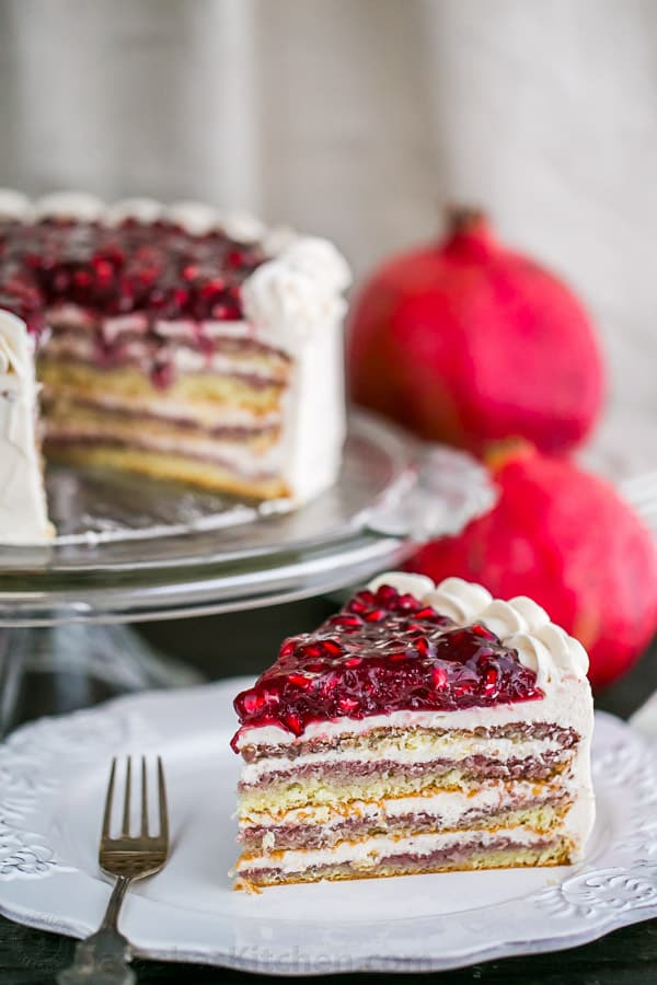 A moist Pomegranate Cake with a crown of glistening pom seeds. Pomegranate cake is fantastic top to bottom and makes for a stunning Christmas Cake! | natashaskitchen.com