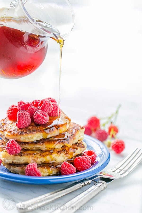 Cottage cheese pancakes served with raspberries and maple syrup