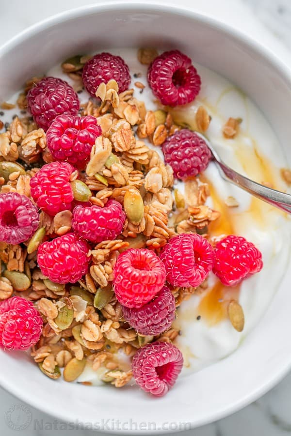 Homemade granola recipe served over yogurt and topped with fresh raspberries and honey