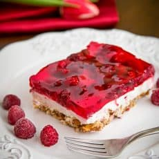 A slice of raspberry pretzel jello on a plate with raspberries beside it