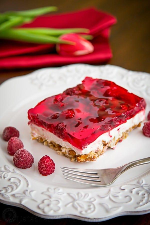 A slice of raspberry pretzel jello on a plate with raspberries beside it