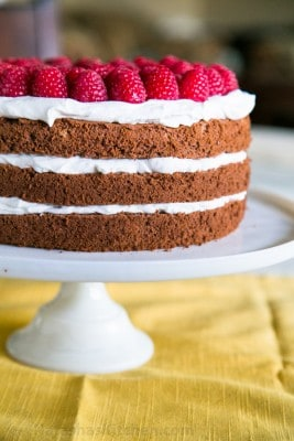 A close up of chocolate layer cake with creme chantilly frosting garnished with raspberries