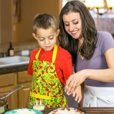 Natasha and her son adding cheese to a dish