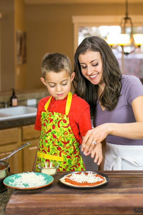 Natasha and her son adding cheese to a dish