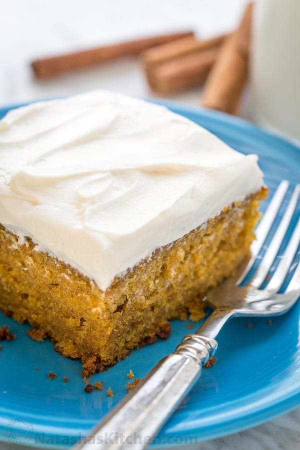 Slice of pumpkin cake on a plate topped with whipped cream cheese frosting