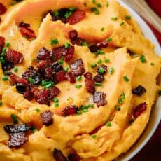 A savory mashed sweet potatoes recipe. Combining yukon and sweet potatoes is brilliant! A perfect holiday side dish. Super easy and seriously delicious. #thanksgiving #natashaskitchen #easysidedish #sweetpotatoes