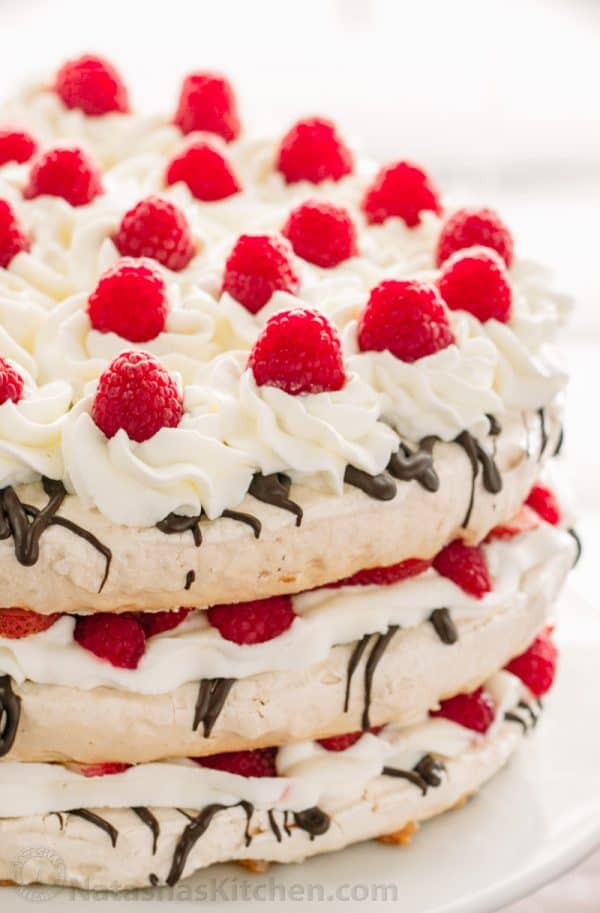 Boccone Dolce has 3 crunchy meringue layers, chocolate, cream and plenty of berries. Drizzled with a berry syrup - this Boccone Dolce Cake is delicious! | natashaskitchen.com