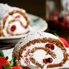 A slice of chocolate cherry roll with rum cream with the whole roll in the background