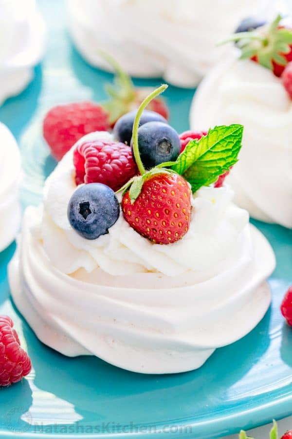Pavlova is a showstopping meringue dessert and is easier than you think! Mini pavlovas have crisp shells and marshmallow centers. They melt-in-your-mouth! | natashaskitchen.com