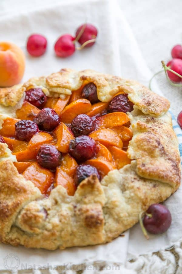 This apricot cherry galette is filled with the juicy apricots and sweet cherries with an easy and flaky pastry crust. Easy apricot cherry galette! | natashaskitchen.com
