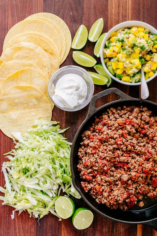 Taco bar toppings with salsa, lime wedges, sour cream, lettuce and soft corn tortillas