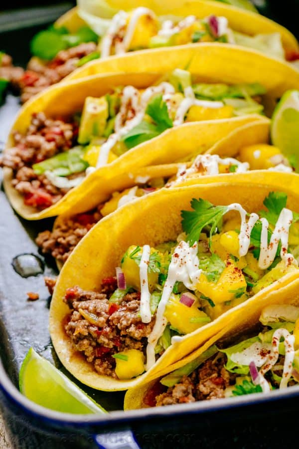 Throw a beef taco PARTY! These juicy beef tacos are loaded and topped with mango salsa. Beef tacos are fun to serve and eat. Fresh, healthy and satisfying! | natashaskitchen.com