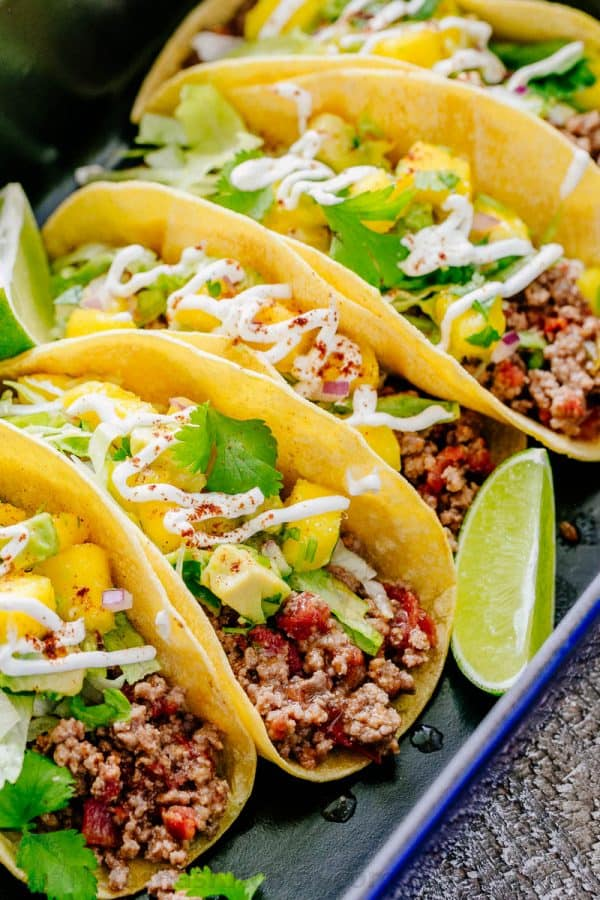 beef tacos on a platter with mango salsa topping and lime wedges