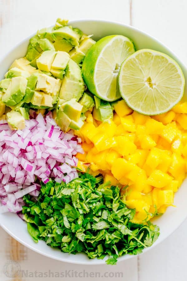Diced Mango, Avocado, Lime, Cilantro, Red Onion, arranged in bowl to make Mango Salsa