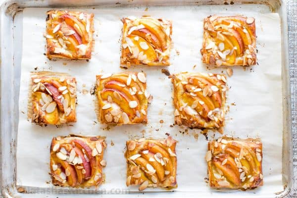 Peach tartlets with juicy peaches, toasted almonds & vanilla glaze over a flaky crust. Puff pastry peach tartlets always get RAVE REVIEWS! Easy, excellent.. | natashaskitchen.com