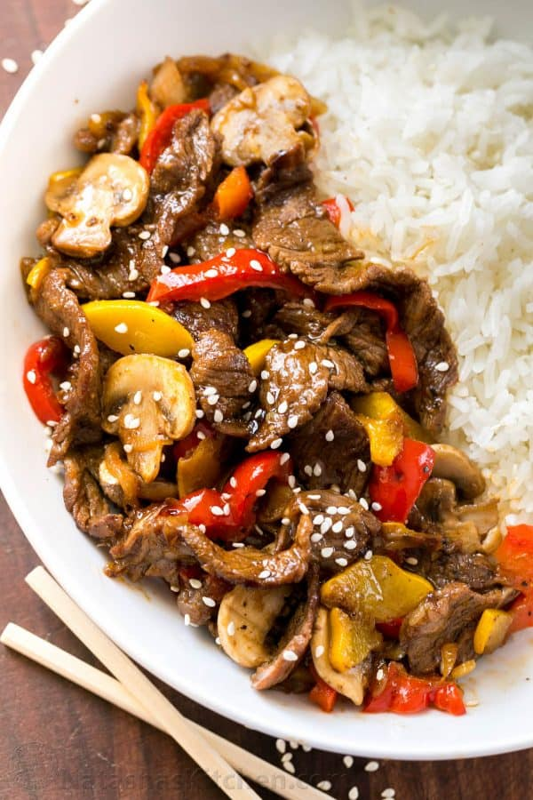 Beef Stir Fry garnished with sesame seeds and served in a bowl with white rice.