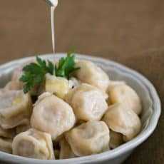A white bowl of Russian chicken pelmeni with butter being poured over the top of them