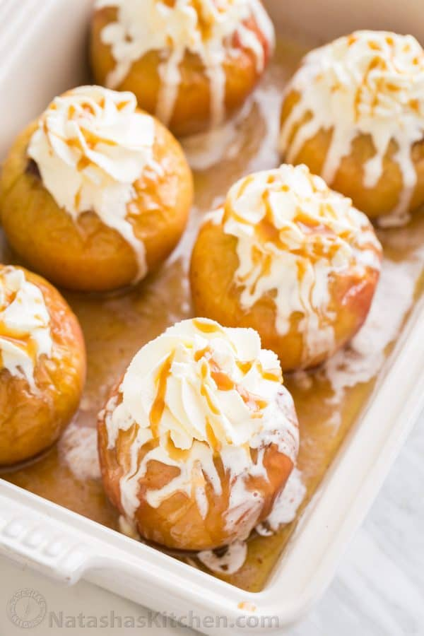 Stuffed roasted apples topped with whipped cream and caramel sauce