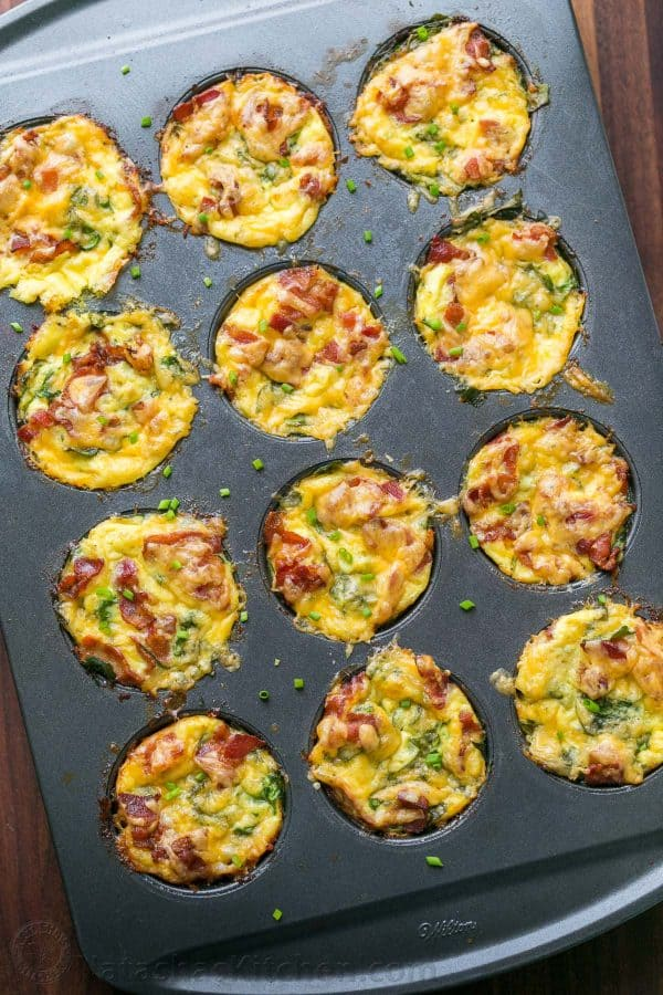 Breakfast egg muffins with potato, spinach, eggs, cheese and crisp bacon in muffin tin
