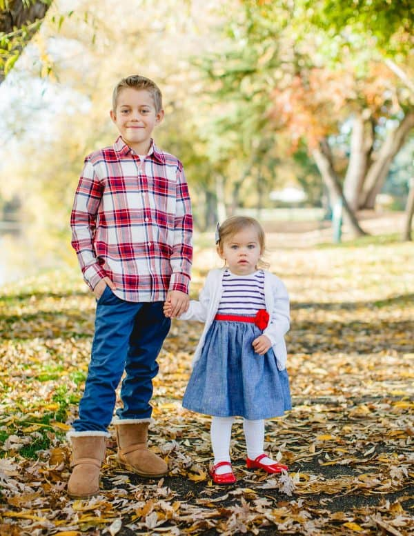 A little boy and girl that is standing fall leaves