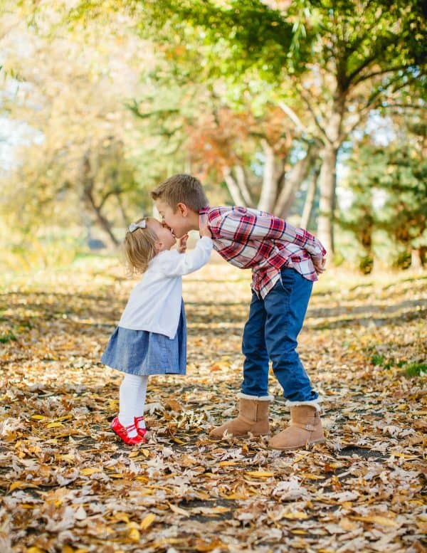 Siblings hugging in the fall leaves