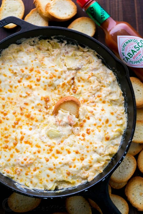 This 1-pan hot shrimp artichoke dip is the perfect holiday appetizer. This shrimp dip is easy, creamy, cheesy, fully loaded, and boy is it ever good! | natashaskitchen.com