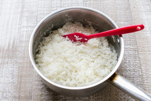 A pot with cooked rice and a spatula in the pot