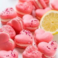 Heart Macarons are easier than you think! Heart-shaped macarons with tangy-sweet lemon buttercream. Includes video tutorial + free printable heart template! | natashaskitchen.com