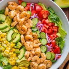 Shrimp Cobb Salad with a chopped romaine base layered with shrimp, avocado, and tomatoes